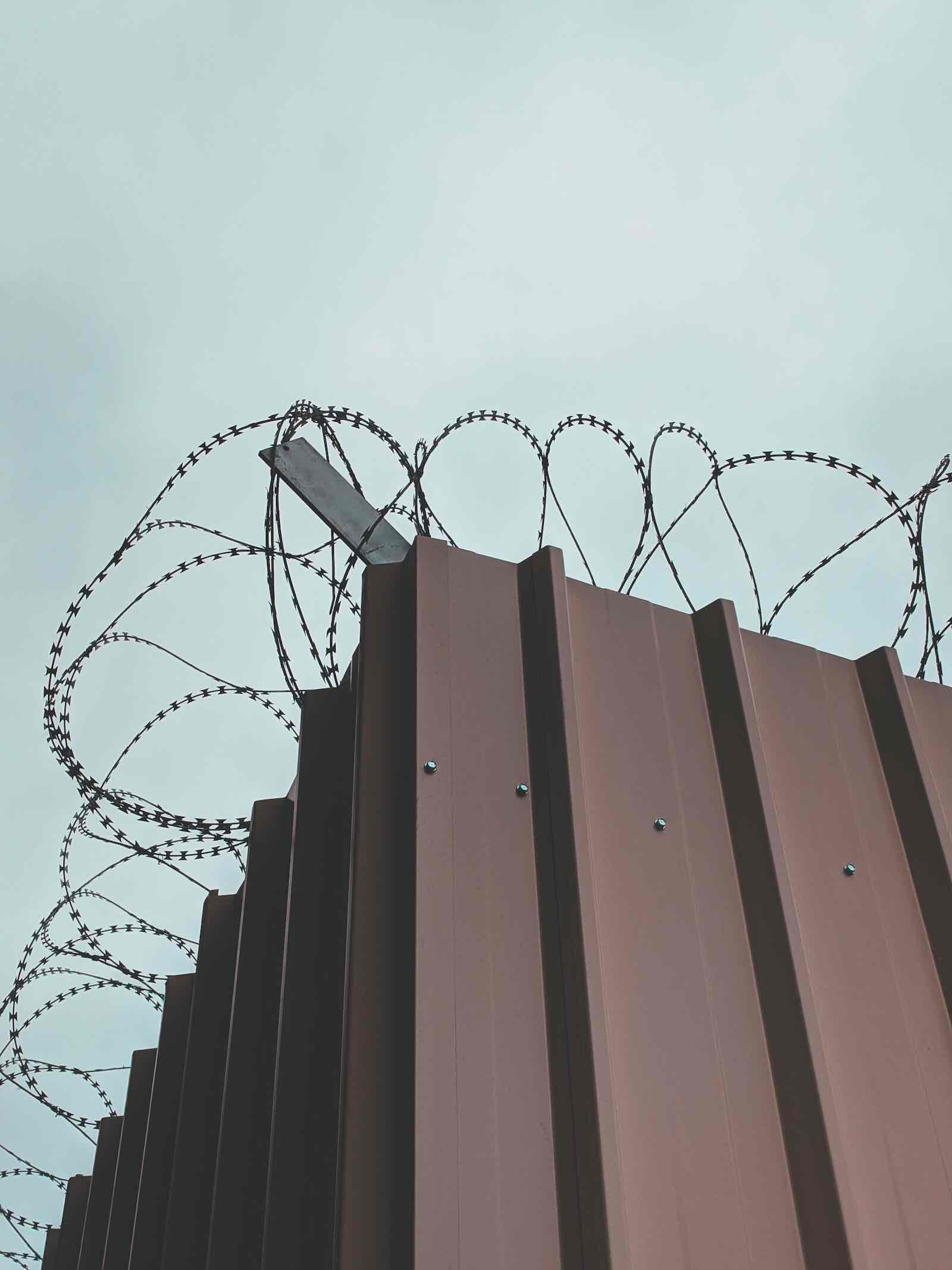 Image of barbed wire above a metal wall