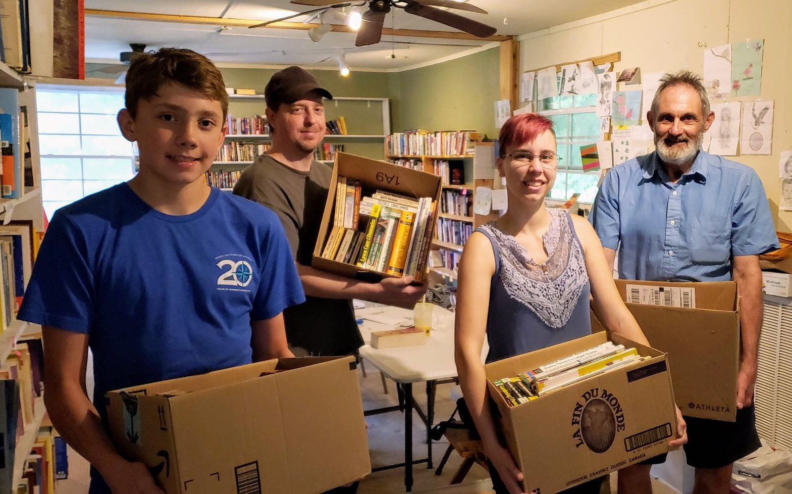 Volunteers showing off boxes of donated books.
